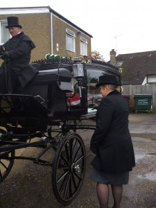 Funeral director with horse drawn hearse